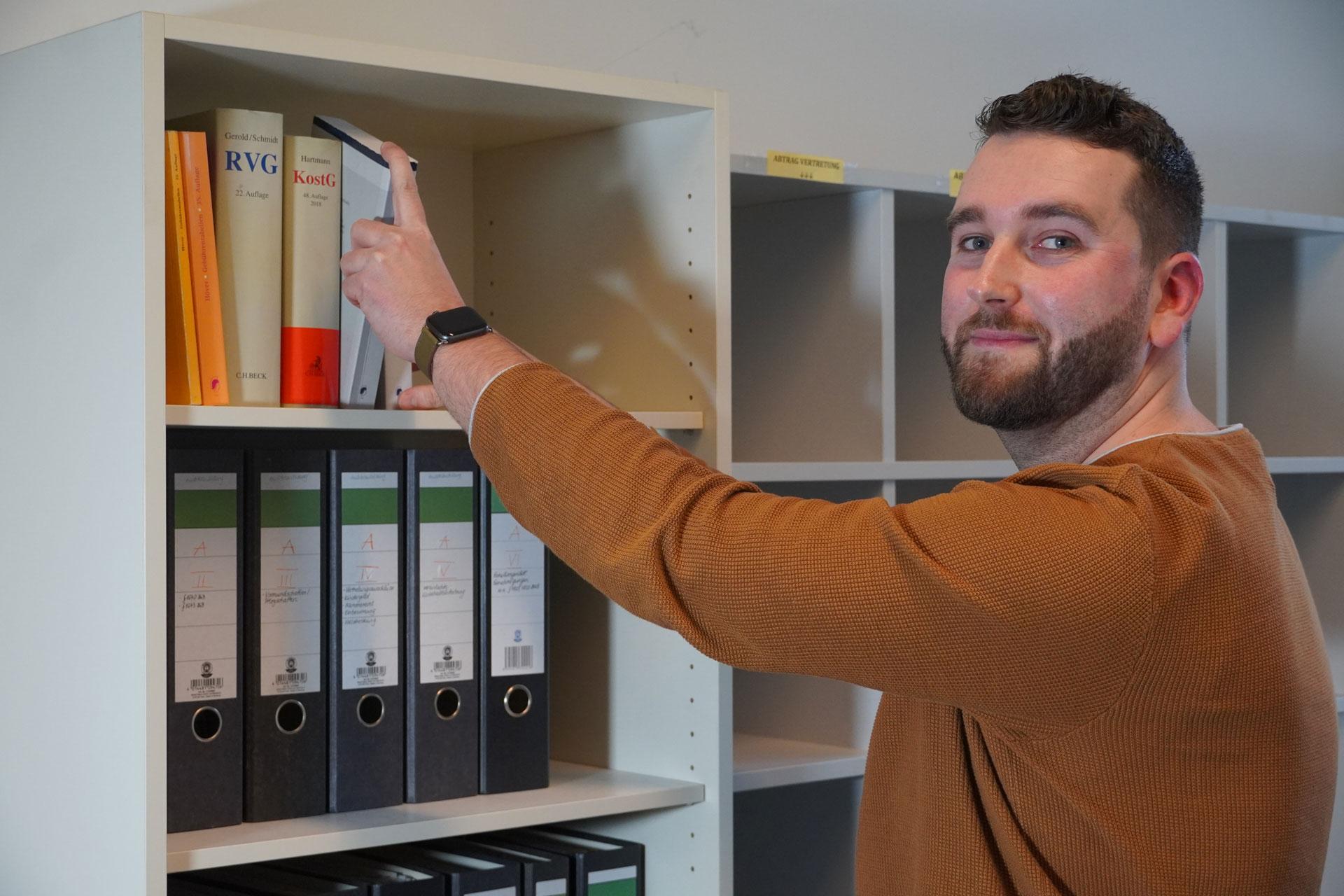 """Das erwartet dich """"Rick Aktenordner""""Alt-Text:Rechtspfleger Rick: Hat im Büro immer alle Paragrafen und Gesetzesbücher griffbereit."""