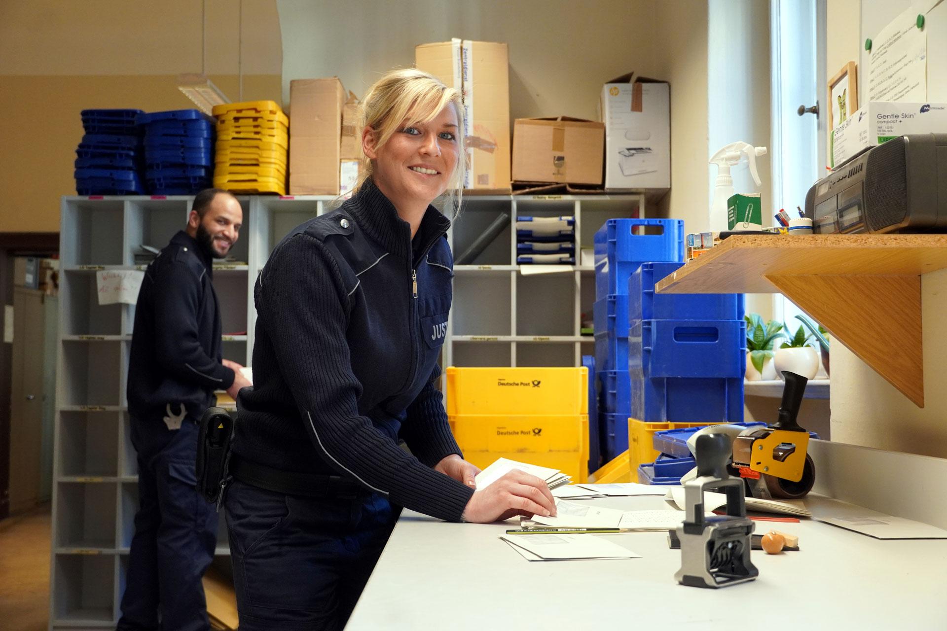 Justizhauptwachtmeisterin Kerstin und Justizwachtmeister Kevin in Uniform: Freuen sich über ihre vielfältigen Aufgaben – wie hier auf der Poststelle